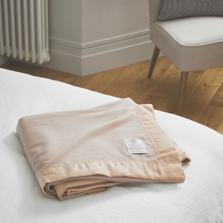 Folded John Atkinsion Lightweight Merino Blankets in Champagne on a bed